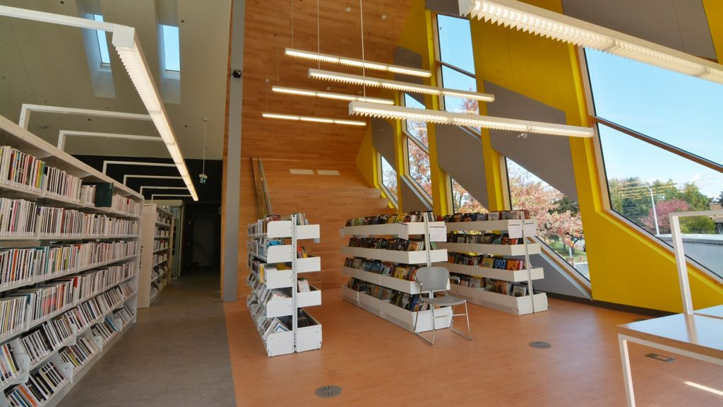 A section of the net-zero library in Varennes, with large windows and lights artfully hung above a row of bookshelves