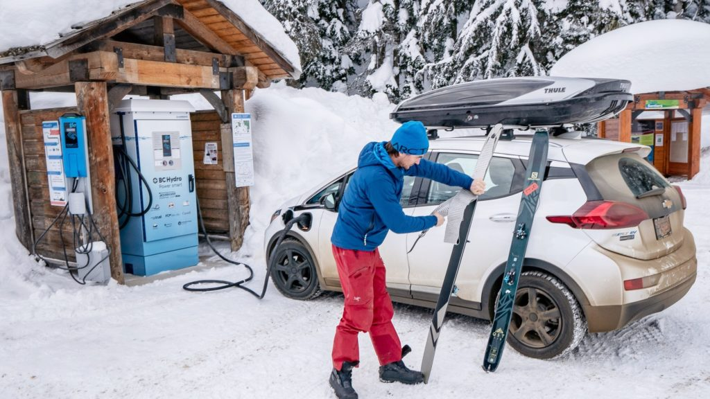 A man charges his car at a charging station while packing up his skis on a snowy winter's day